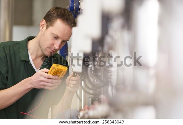 Hochtechniker reparieren Landmaschinen in einem Gewächshaus