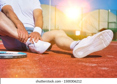 Senior tennis player sitting with ankle pain in court with yellow lens flare in background