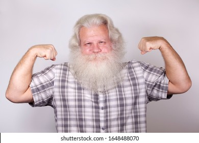 Senior thickset Caucasian happy man with splendid grey hair and beard on grey background, demonstrating his big biceps. Attractive elderly European handsome smiling people close up. Beautiful portrait
