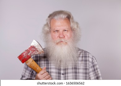 Senior thickset Caucasian man with splendid grey hair and beard on grey background with worn red ax in hand. Attractive elderly European people close up. Macro portrait of grey-head Santa Claus.