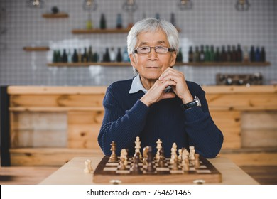 senior thoughtful asian man with chess board sitting in bar
