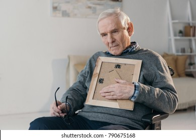 Senior thoughtful man sitting in chair and holding old photo frame