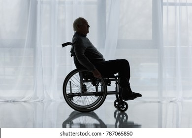 Senior thoughtful man in wheelchair in front of window