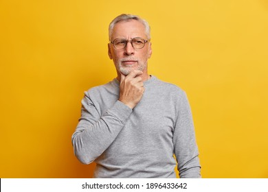 Senior thougthful man holds chin and looks pensively aside makes plannings wears spectacles and casual grey jumper isolated over vivid yellow background. Handsome grandfather considers something