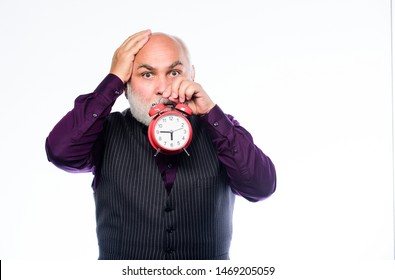 Senior timekeeper. time and age. Timekeeping. mature bearded man with alarm clock. retirement. watchmaker or watch repairer. mature man with beard clock show time. time management. business startup.