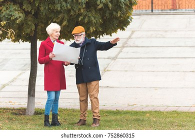 senior tourist couple looking at map while standing in park