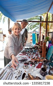 Senior tourist couple visiting artisan market on holiday city break, shopping souverins outdoors, smiling. Consumer mature mand and woman retirement activities, travel recreation leisure lifestyle.