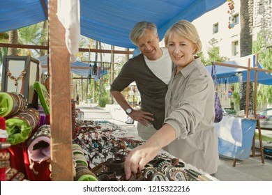 Senior tourist couple visiting flea market on holiday city break, shopping souverins outdoors, smiling. Consumer mature mand and woman discovery activities, travel recreation leisure lifestyle.