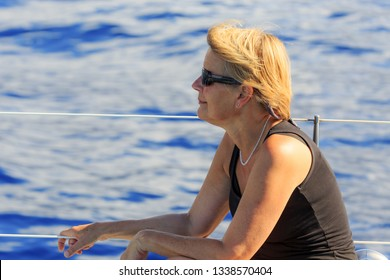 Senior tourist enjoys a whale and dolphin watching catamaran excursion from Funchal, on the island Madeira in summer