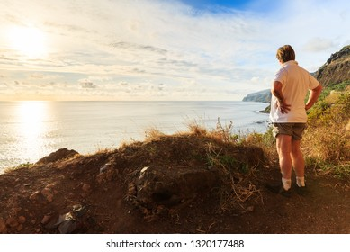 Senior tourist hiking at the coastline cliffs at Tuneis antigos near Ponta do Sol on the east coast of Madeira island, at sunset with the atlantic ocean in summer