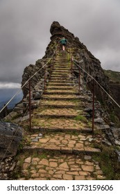 Senior tourist in the mountains of Madeira at Pico do Areeiro (Arieiro), while hiking to Pico Ruivo on a cloudy summer day with ominous sky and storm weather