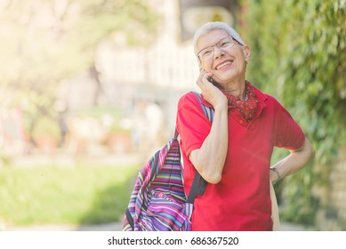 Senior tourist woman in a foreign city having a chat over her phone