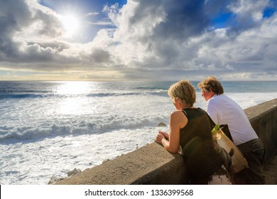 Senior tourists looking out over the Atlantic ocean in the afternoon at sunset, on the island Madeira in summer