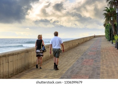 Senior tourists walking on the boulevard in the evening at sunset, on the island Madeira in summer