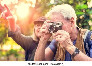 Senior trekker taking a photo with a film camera