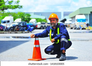 Senior truck driver with safety hat wearing safety vest put the arm on the traffic cone.