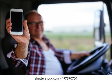 Senior truck driver showing mobile phone while driving.