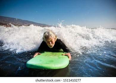 senior trying to surf a wave on the sea at the beach alone with black wetsuit and green surftable - vacation at the sea and active retired man