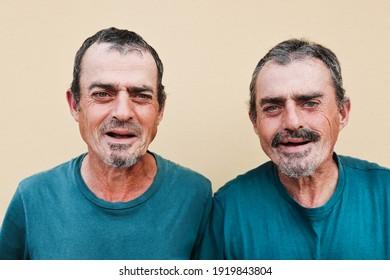 Senior twin men smiling on camera - Focus on faces