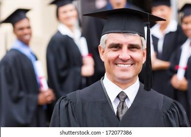 senior university professor in front of group of graduates