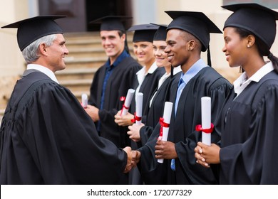 senior university professor handshaking with young graduates