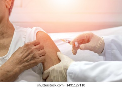 Senior vaccination concept. Elderly getting immune vaccine at arm for flu shot, pneumonia, and shingles(MMR) in hospital by nurse. Doctor giving an injection to older people patient in clinic.