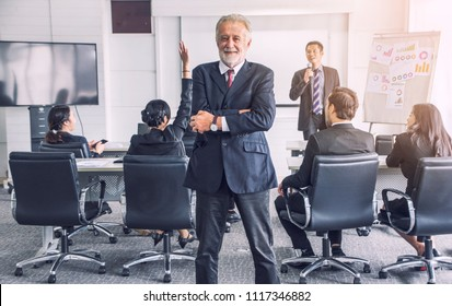 Senior Vice President  standing and smiling  cross arm confident with Successful team leader and business owner leading informal in-house business meeting.
