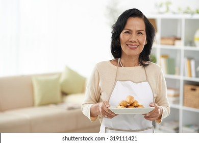 Senior Vietnamese housewife with a plate of eclairs