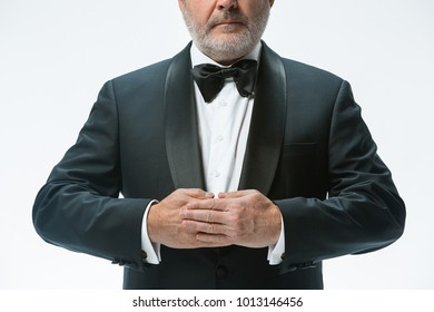 The senior waiter holding white towel and standing isolated on white studio background. sign language in the restaurant. Gesture means - accepted the order