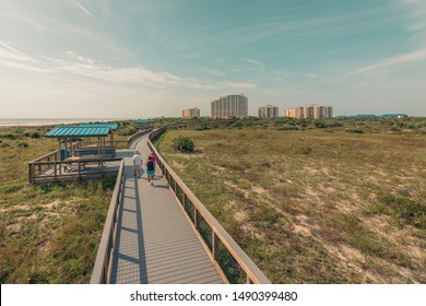 Senior walkers fit and active walking on the Smyrna Dunes boardwalk at New Smyrna Beach, Florida.