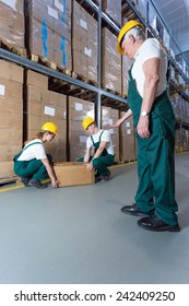 Senior warehouse worker controlling young co-workers in storeroom