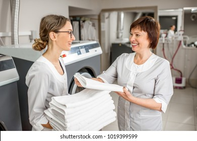 Senior washwoman making up clean towels with young assistant in the hotel laundry