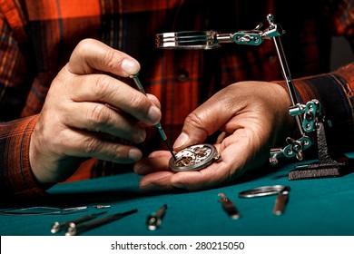 Senior watchmaker repairing an old pocket watch