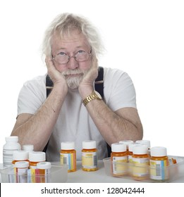 senior wearing glasses with a lot of prescription bottles of pills isolated on white