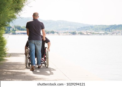 Senior In Wheelchair Spending Time Outdoors With His Nurse