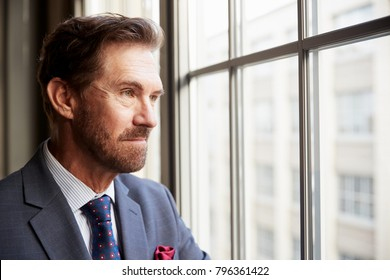 Senior white businessman looking out of window, close up