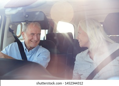 Senior white couple driving in their car smiling to each other, seen through front windscreen