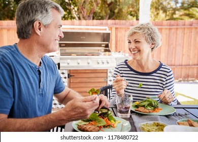 Senior white couple eating together at a table in the garden