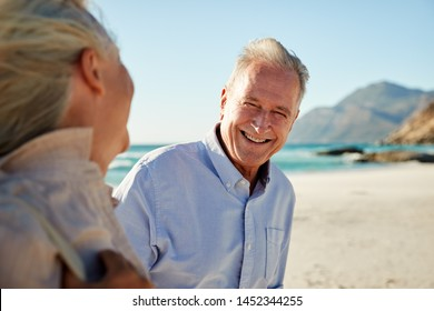 Senior white couple walking on a beach, looking at each other and smiling, waist up, close up