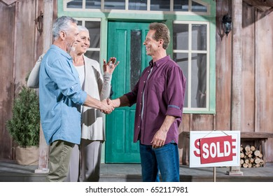 senior wife holding keys of new house while her husband shaking hands with saleman