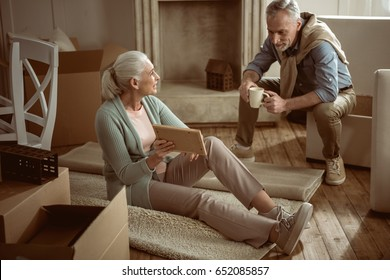 senior wife showing old photo to her husband while taking break from packing cardboard boxes, moving out concept