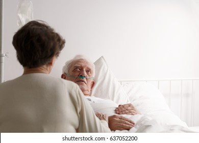 Senior wife supporting dying husband sitting by the hospital bed