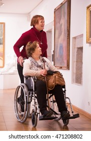 Senior woman 60-70 years old and her handicapped female friend whatching art works