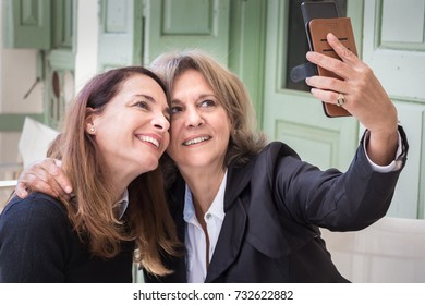 A senior woman, 61, taking a selfie with her mobile together with her 46 years old friend, lifestyle concept.