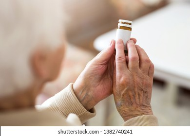 Senior woman about to take her medication - Shutterstock ID 1382740241
