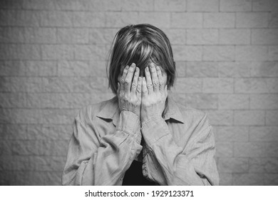 Senior woman addict and alcoholism alone depression stress sitting on the floor with her head in her hands. headache, dizziness, migraine. Social documentary concepts black and white
