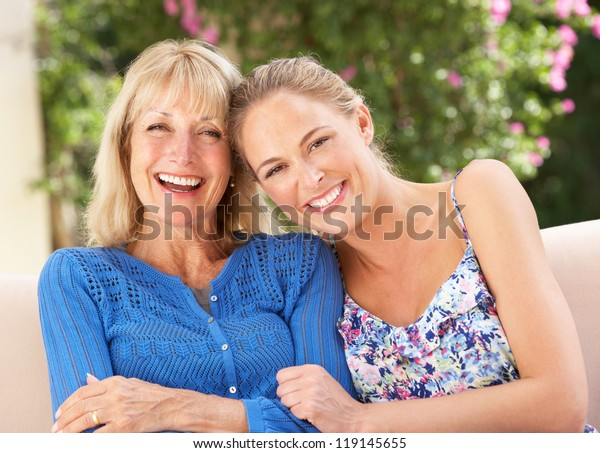 Senior Woman With Adult Daughter Relaxing On Sofa At Home
