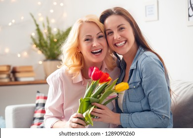 Senior woman and adult woman together at home celebration sitting on sofa hugging holding flowers bouquet laughing joyful close-up