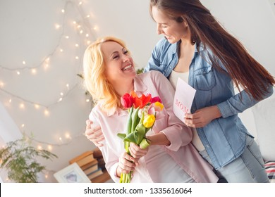 Senior woman and adult woman together at home celebration standing daughter hugging mom holding bouquet of tulips smiling happy giving greeting card