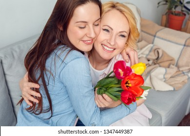 Senior woman and adult woman together at home celebration sitting on sofa hugging holding bouquet of flowers smiling joyful closed eyes close-up